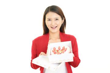 ケーキを持つ笑顔の女性