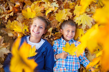 Cute boy and girl in autumn park