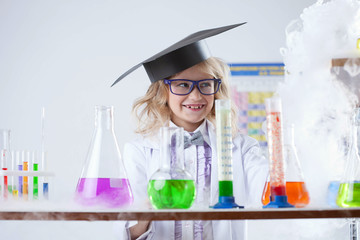 Smiling little chemist puts experiments in lab