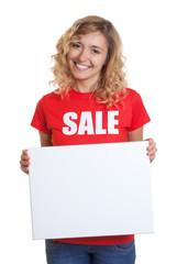 Blonde Frau im Sales-Shirt hält Werbetafel