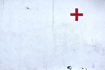 Red Cross Symbol Painted on Old Hospital Wall