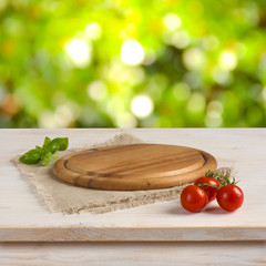 Kitchen table with round board over green bokeh background