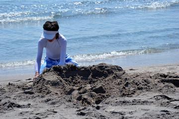 L'été indien - Portrait d'enfant seul jouant à la plage