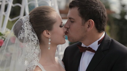 The groom kisses the bride in a beautiful wedding ceremony