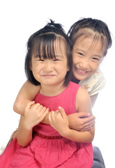Two happy asian little sisters hugging, siblings love together