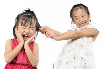 Siblings teasing, asian little girl pulling her sister's hair