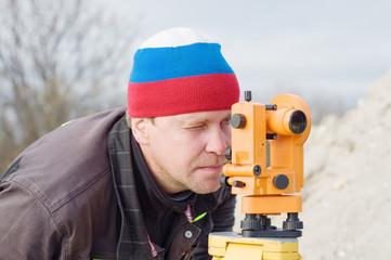 Инженер на стройке делает измерения с помощью теодолита