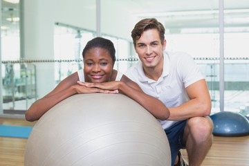 Personal trainer and client smiling at camera with exercise ball