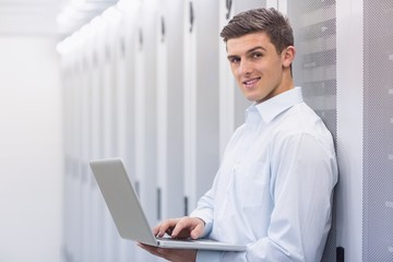 Smiling technician typing on his notebook