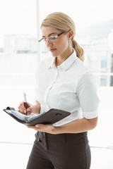 Businesswoman writing in diary at office