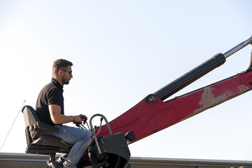 industrial worker at the controls of a crane
