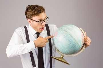 Geeky businessman pointing to globe