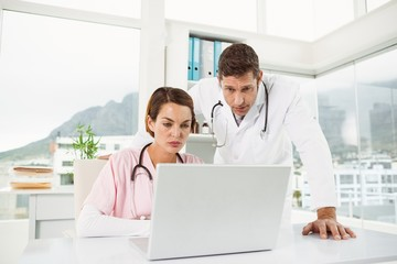 Doctors using laptop together at medical office