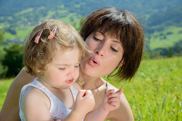 a beautiful mom and daughter play with a flower in nature