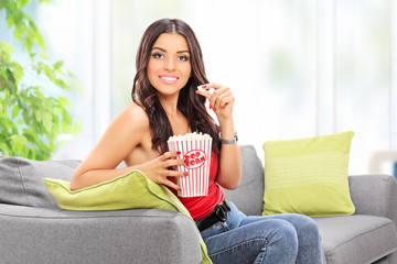 Woman eating popcorn seated on sofa at home