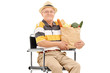Senior holding a grocery bag seated in wheelchair