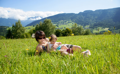 a beautiful mother and daughter lying on the grass