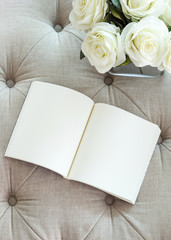 Book on sofa with white rose flower