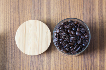 Coffee beans in glass on wood background