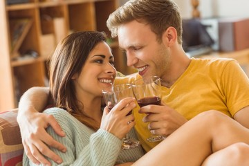 Young couple cuddling on the couch with red wine