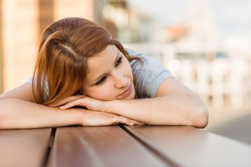Day dreaming casual redhead lying on bench