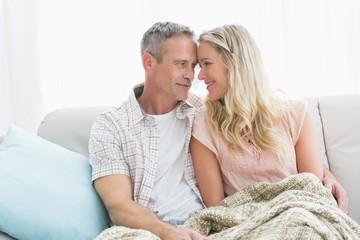 Affectionate couple sitting on sofa under blanket