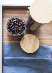 Coffee beans in glass on wood tray