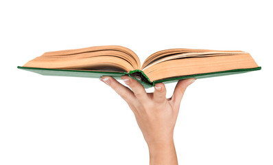 Female hand holding an open vintage book in green cover. Concept