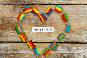 Happy birthday card with heart made of colorful candies on wood