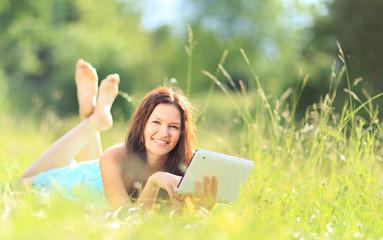 Happy woman reading e-book in the park