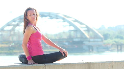 Young woman doing yoga on riverbank, rear view.