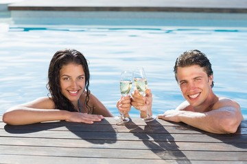 Couple toasting champagne in swimming pool