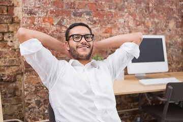 Businessman with hands behind head in office