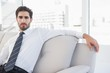 Concentrated businessman sitting on couch