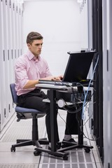 Technician sitting on swivel chair using laptop