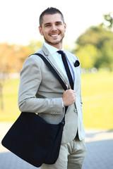 Young urban businessman running in street smiling wearing jacket