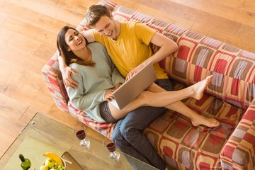Young couple cuddling on the couch with laptop