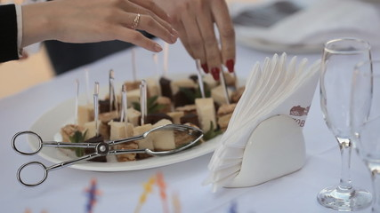 The waiters in the restaurant prepares canapes from cakes
