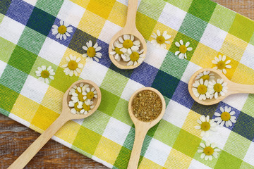 Chamomile flowers on wooden spoons on checkered cloth