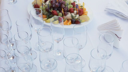 Table layout in a restaurant with fruit canapes and glasses of