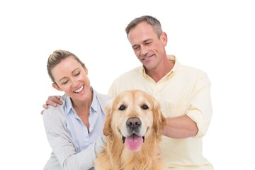 Smiling couple petting their golden retriever