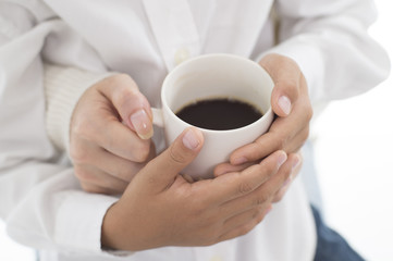 The hands of parents and children with hot coffee