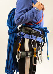 Young woman in climbing equipment on white background