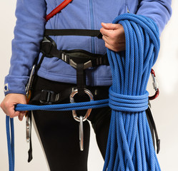 Young woman in climbing equipment with climbing rope in hands