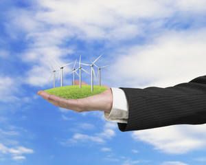 hand holding group of wind turbines on grass