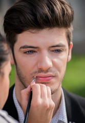 Young attractive man during a makeup session