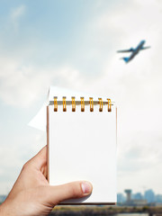 white blank notebook in man hand and airport background