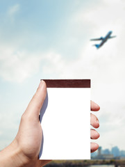 white blank notebook in woman hand and airport background