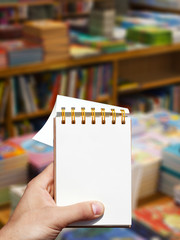 white blank vertical notebook in man hand and books background