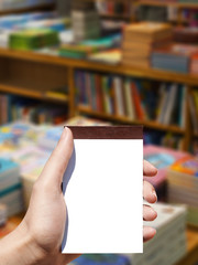 white blank vertical notebook in woman hand and books background